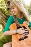 Smiling with her guitar Royalty Free Stock Images