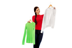 Smiling hesitant young woman holding two shirts.  Stock Image