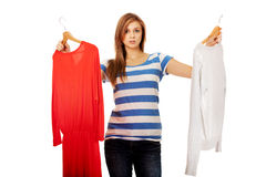 Smiling hesitant young woman holding two shirts.  Royalty Free Stock Image