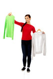 Smiling hesitant young woman holding two shirts.  Royalty Free Stock Images