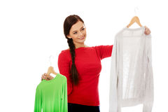Smiling hesitant young woman holding two shirts.  Stock Photos