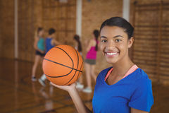Smiling high school girl holding a basketball while team playing in background stock photography