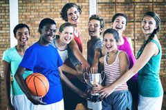 Smiling high school kids holding trophy in basketball court stock images