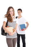 Smiling High School Students on White Background. Two smiling teenagers with school supplies isolated on white in studio Stock Image