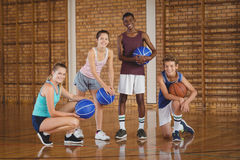 Smiling high school team holding basketball in the court Stock Image