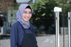 Smiling Hijab Arabic woman with apron posing in front of glass door welcoming a costumer. Portrait of young muslim business woman waitress in black apron ready royalty free stock photography
