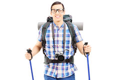 Smiling hiker with backpack and hiking poles walking Royalty Free Stock Photo