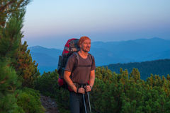 Smiling hiker with backpack  looks into the distance in the moun Royalty Free Stock Photography