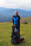 Smiling hiker with backpack is resting Stock Photos