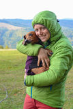 Smiling hiker with dog in the mountains. Royalty Free Stock Image