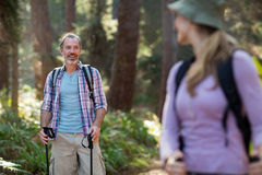 Smiling hiker hiking with trekking poles Stock Photo