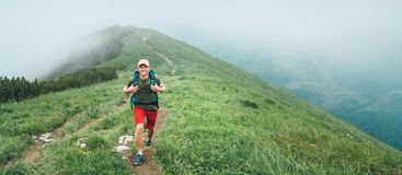 Smiling hiker man walking by the foggy cloudy weather mountain range path with backpack. Active sport backpacking healthy stock photos