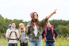Smiling hikers with backpacks pointing finger Stock Photos
