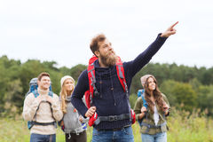Smiling hikers with backpacks pointing finger Royalty Free Stock Photography