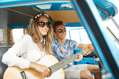 Smiling hippie couple with guitar in minivan car Royalty Free Stock Image