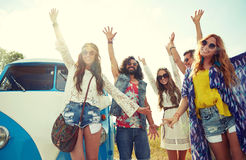 Smiling hippie friends having fun over minivan car Stock Images