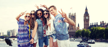 Smiling hippie friends with selfie stick in london Stock Photography