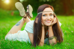 Smiling hippie girl. On green grass Royalty Free Stock Photo
