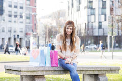 Smiling hippie girl with shopping bags in the street. Stock Image