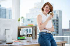 smiling hipster business woman drinking coffee in her office Royalty Free Stock Photo