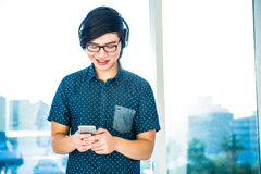 Smiling hipster businessman listening music Stock Photography