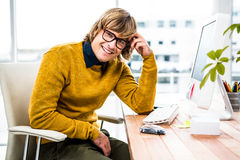 Smiling hipster businessman sitting at his desk Stock Photo