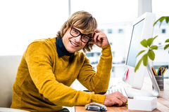 Smiling hipster businessman sitting at his desk Stock Images