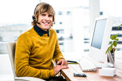 Smiling hipster businessman using headset. In his office Stock Photo