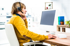 Smiling hipster businessman using headset. In his office Stock Photography