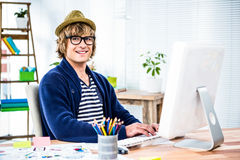 Smiling hipster businessman using his computer Stock Images