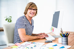 Smiling hipster businessman using his computer Royalty Free Stock Photo