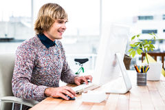 Smiling hipster businessman using his computer Royalty Free Stock Image