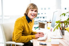 Smiling hipster businessman using his computer Royalty Free Stock Images
