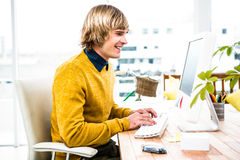 Smiling hipster businessman using his computer Stock Image