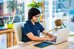 Smiling hipster businessman using laptop and graphic tablet Royalty Free Stock Photo