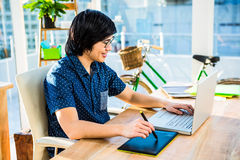 Smiling hipster businessman using laptop and graphic tablet Royalty Free Stock Image