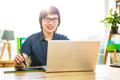 Smiling hipster businessman using laptop and graphic tablet Stock Image