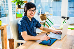 Smiling hipster businessman using laptop and graphic tablet Royalty Free Stock Photography