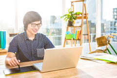 Smiling hipster businessman using laptop and graphic tablet Royalty Free Stock Photos
