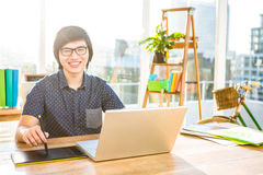 Smiling hipster businessman using laptop and graphic tablet Stock Photo