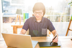 Smiling hipster businessman using laptop and graphic tablet Stock Images