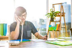 Smiling hipster businessman writing and holding telephone Stock Photos