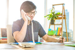 Smiling hipster businessman writing and holding telephone Royalty Free Stock Photography