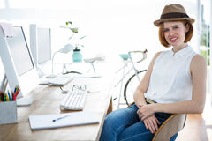 Smiling hipster businesswoman sitting at her desk Stock Photos