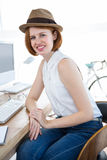 Smiling hipster businesswoman sitting at her desk Royalty Free Stock Photos