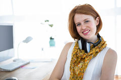 Smiling hipster businesswoman sitting at her desk Stock Image