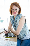 smiling hipster businesswoman writing on a digital drawing tablet Royalty Free Stock Photography