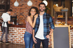 Smiling hipster couple in front of barista. Portrait of smiling hipster couple in front of barista at coffee shop stock photos