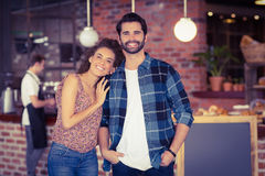 Smiling hipster couple in front of barista. Portrait of smiling hipster couple in front of barista at coffee shop royalty free stock photos