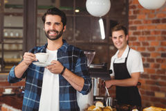 Smiling hipster drinking coffee in front of barista Royalty Free Stock Photography